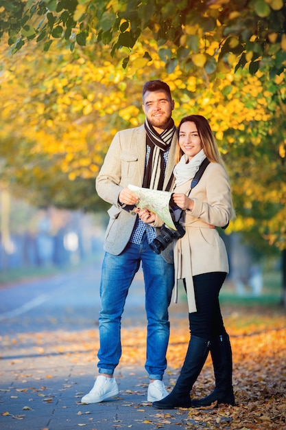 Couple with map and camera in city autumn alley. Premium Photo