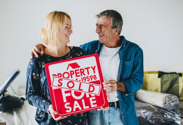 Couple with a property for sale sign Premium Photo
