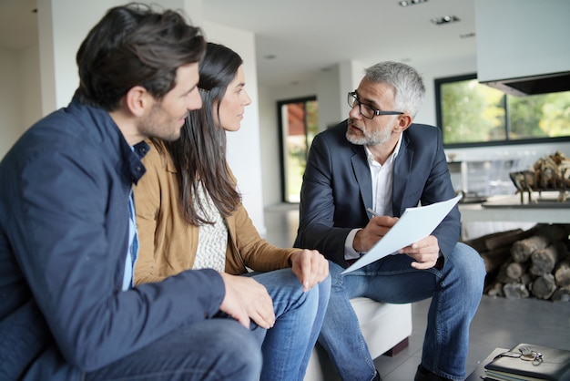 Couple with real-estate agent looking at contract in modern house Premium Photo