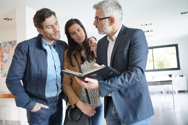 Couple with real-estate agent visiting modern house Premium Photo