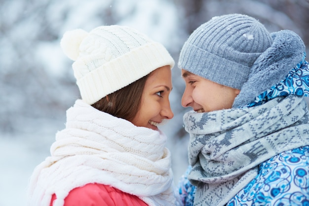 Couple with scarves and woolen hats looking at each other Free Photo