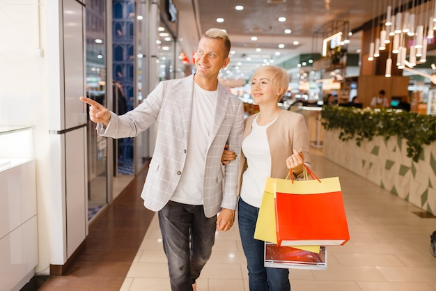 Пара с хозяйственными сумками в ювелирном магазине Premium Фотографии