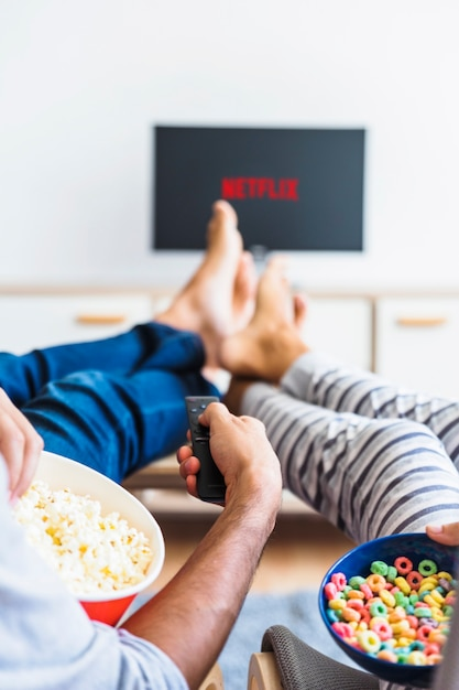 Couple with snacks using remote control while watching series Free Photo