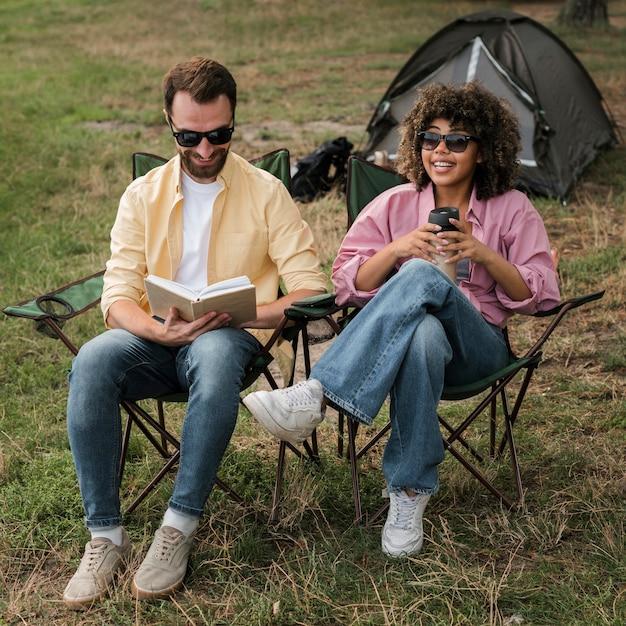 Coppia con occhiali da sole leggendo e bevendo durante il campeggio all'aperto Foto Gratuite