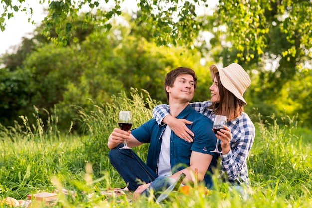 Couple with wine glasses hugging in nature Free Photo