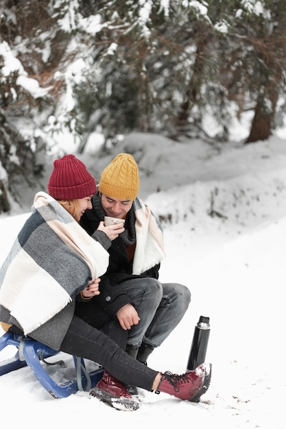Couple with winter clothes sitting on sleigh and drink tea Free Photo