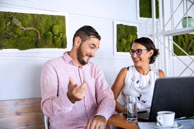 Пара работает из дома, используя ноутбук, пить кофе и говорить о работе. деловая встреча на кухне во время вспышки пандемии коронавируса Premium Фотографии