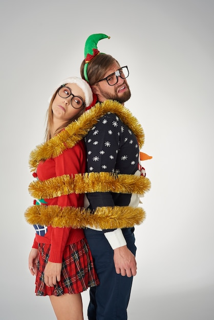 Couple wrapped in golden christmas chain Free Photo