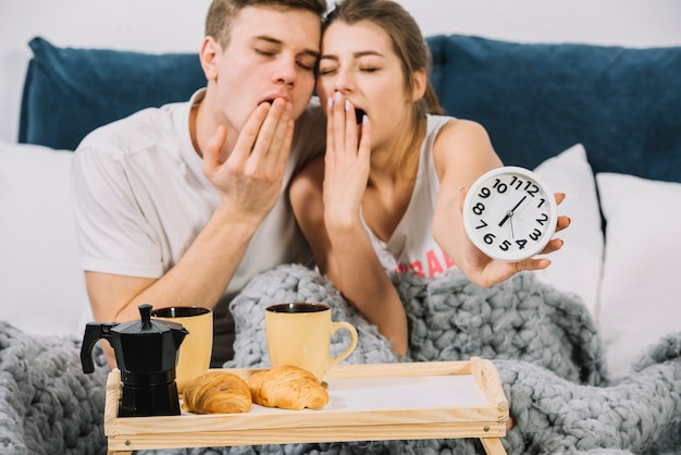 Couple yawning in bed with food tray Free Photo