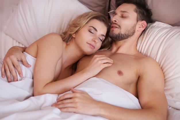 Coppia di giovani adulti che dormono in camera da letto Foto Gratuite