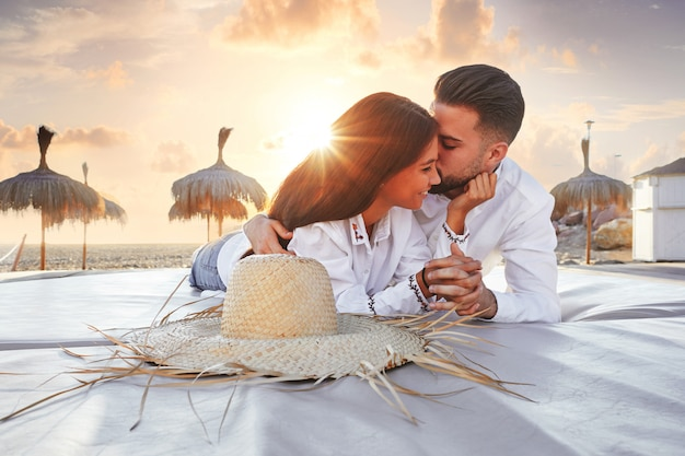 Couple young on beach lounge sunset Premium Photo