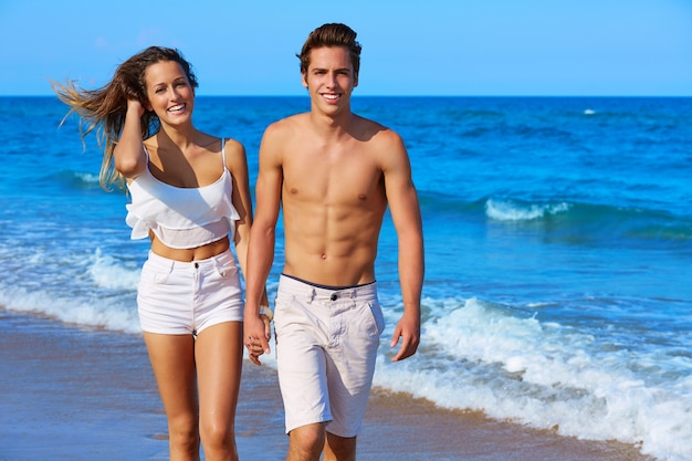 Couple young walking on the beach shore Premium Photo