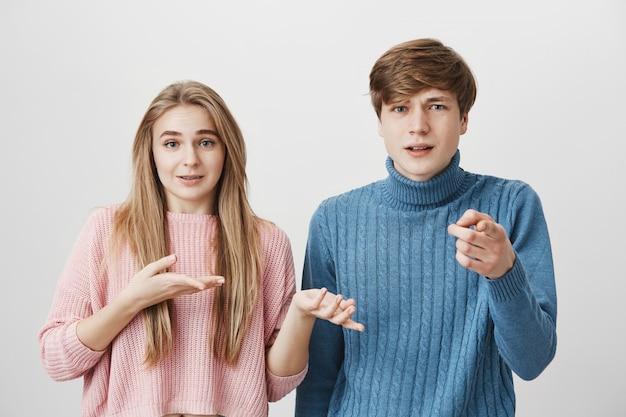 Un paio di giovani che indicano con il dito indice. giovane maschio biondo che punta alla telecamera con espressione del viso insoddisfatto Foto Gratuite
