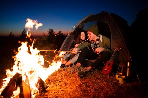 Coupleき火と一緒に若いカップル 無料写真
