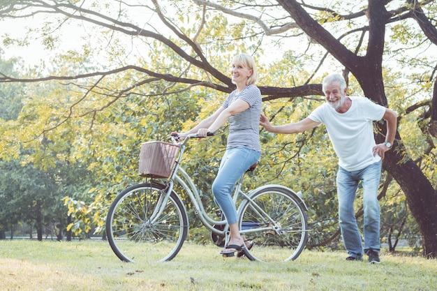 高齢者のカップルは一緒に自転車に乗っています。 Premium写真