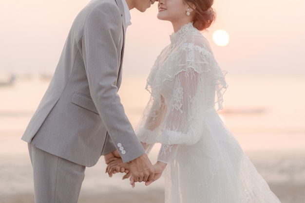 Couples holding hands and kissing on the beach by the sea. love concept Premium Photo