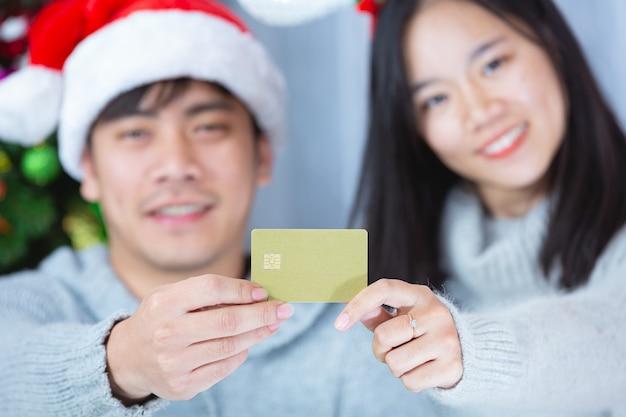 一緒にクレジットカードを保持しているクリスマス帽子のカップル 無料写真
