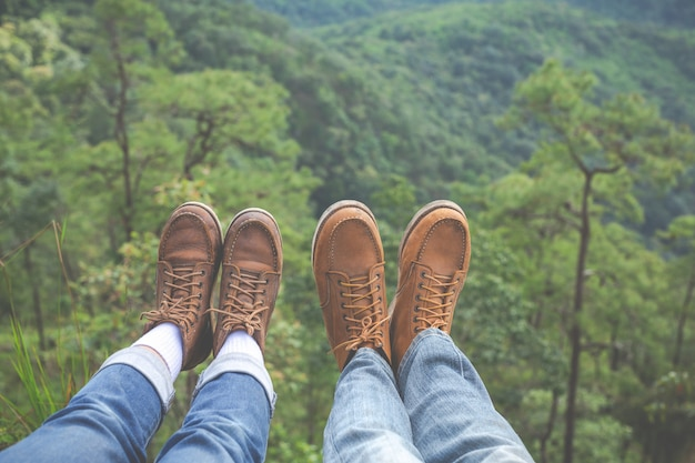 Couples raise their feet pointing to the hillside in tropical forests, hiking, traveling, climbing. Free Photo