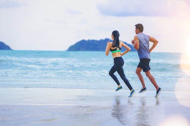 Couples runner jogging at the beach with sunset. Premium Photo