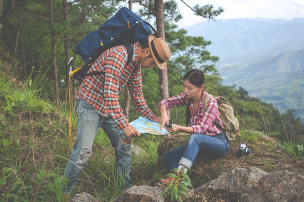 Couples see a map in a tropical forest with backpacks in the forest. adventure, hiking, climbing. Free Photo
