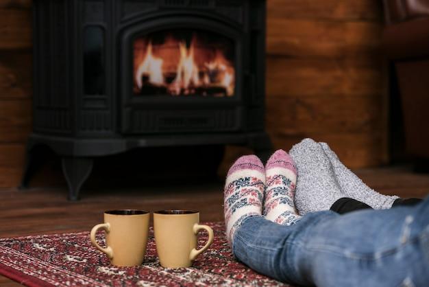 Couples warming feet next to fireplace Free Photo