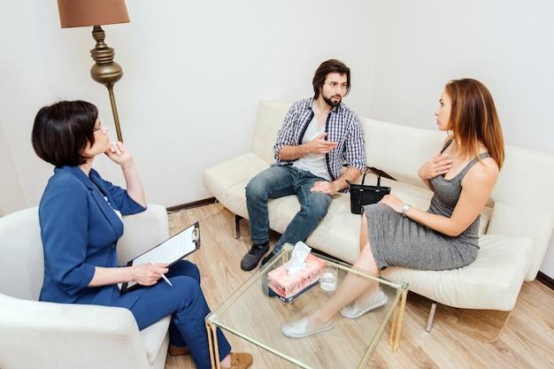 Couplt сидит и разговаривает друг с другом. мужчина указывает на женщину. она указывает на себя. доктор слушает их очень внимательно. Premium Фотографии
