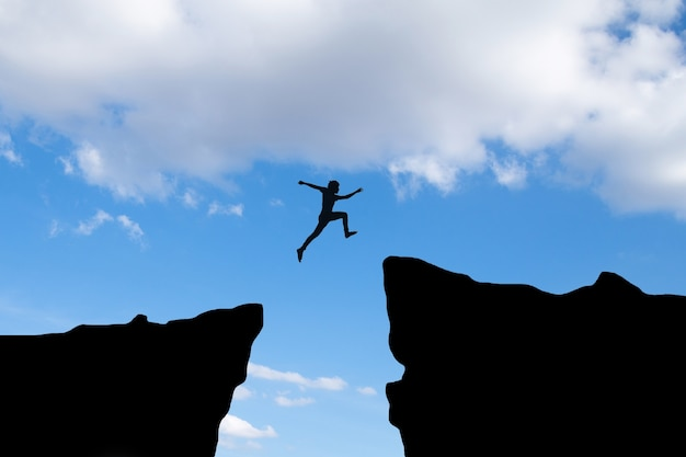 Courage man jump through the gap between hill ,business concept idea Free Photo