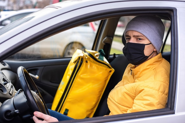 Courier in the car with black medical mask, delivery backpack on the seat. food delivery service Free Photo