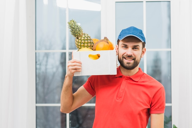Courier carrying fruits on shoulder Free Photo