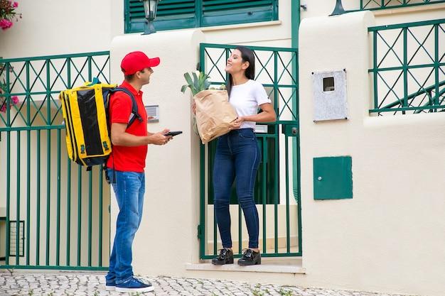 고객에게 음식과 함께 종이 패키지를 배달하는 택배. 태블릿 및 식료품가 게에서 음식을 가진 여자 회의 배달 남자. 배송 또는 배달 서비스 개념 무료 사진