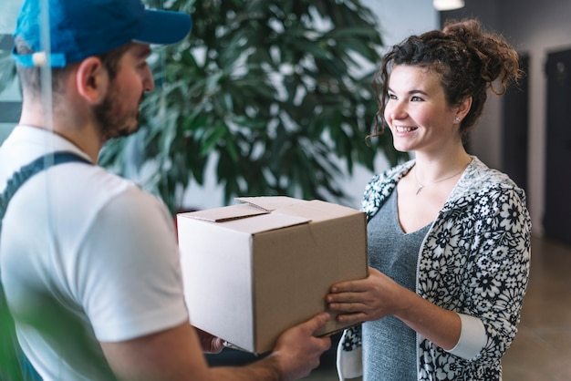 Courier delivering parcel to woman Free Photo