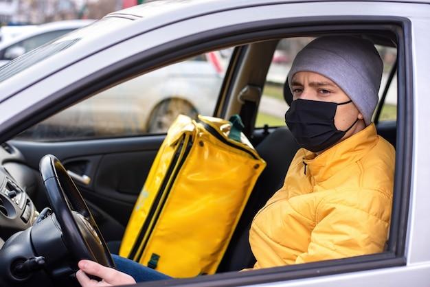 Курьер в машине с черной медицинской маской, доставка рюкзак на сиденье. служба доставки еды Бесплатные Фотографии