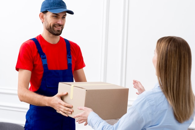 Courier man delivering a cardboard box to a woman Free Photo