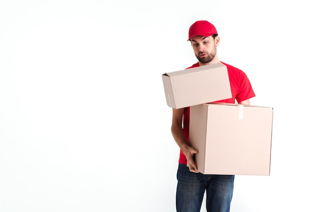 Courier man trying to hold all the parcel post boxes Free Photo