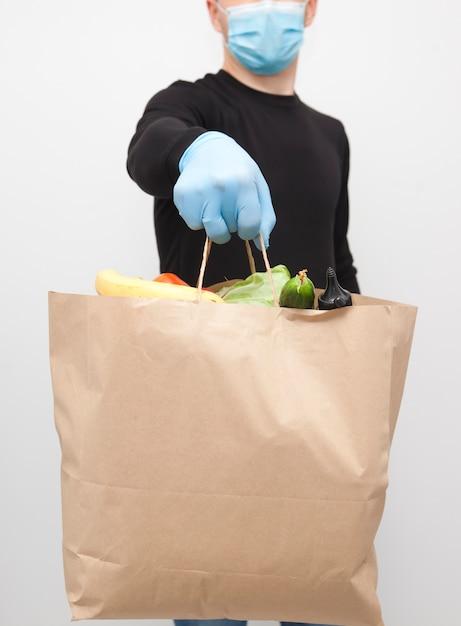 Курьер в маске и перчатках держит бумажный пакет Premium Фотографии