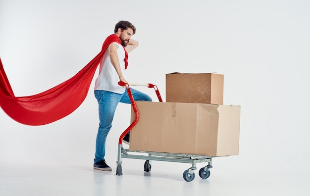 Courier with cardboard boxes in cargo trolley and red superhero cloak Premium Photo