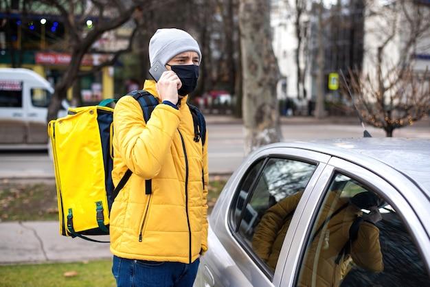 Corriere con zaino giallo e mascherina medica nera vicino a un'auto che parla al telefono Foto Gratuite