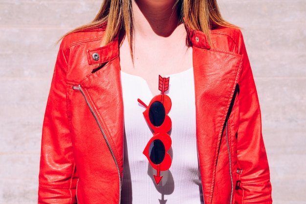 Covered neckline of woman with funny red cheeky glasses with cupid arrow. Premium Photo