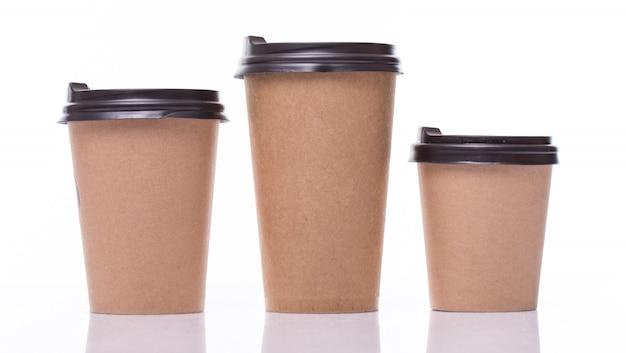 Покрытые бумажные кофейные чашки разных размеров, изолированные на белом Бесплатные Фотографии
