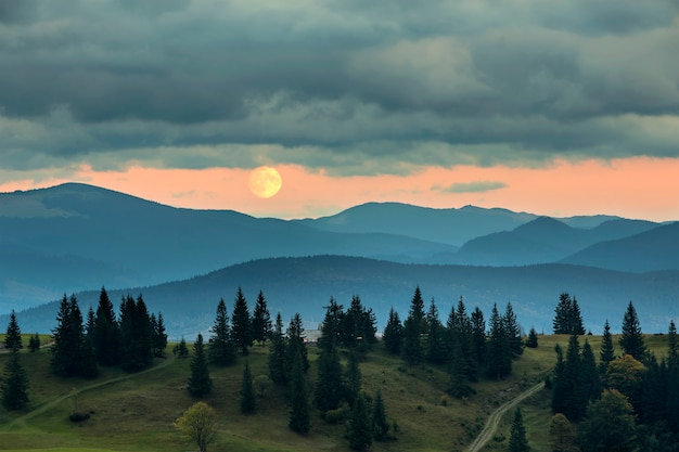 Covered with mist mountains at moonrise, big moon on bright orange sky over tall Premium Photo