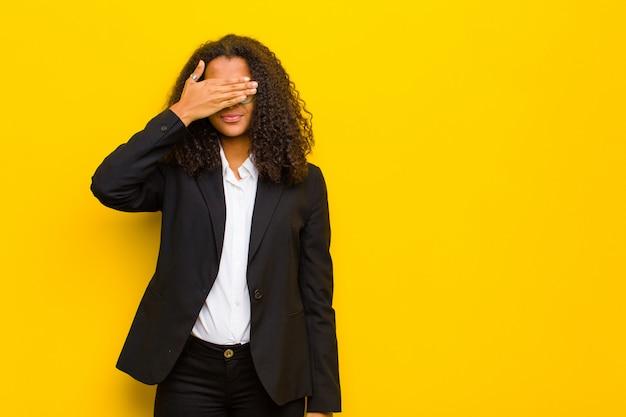 片方の手で目を覆って怖がったり不安を感じたり、不思議に思ったり、驚きを待っている Premium写真