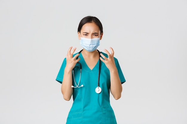 Covid-19、コロナウイルス病、医療従事者の概念。怒って腹を立てているアジアの女性医師、医療用マスクとスクラブの医師、握りこぶしは激怒し、猛烈な白い背景に見えます。 Premium写真