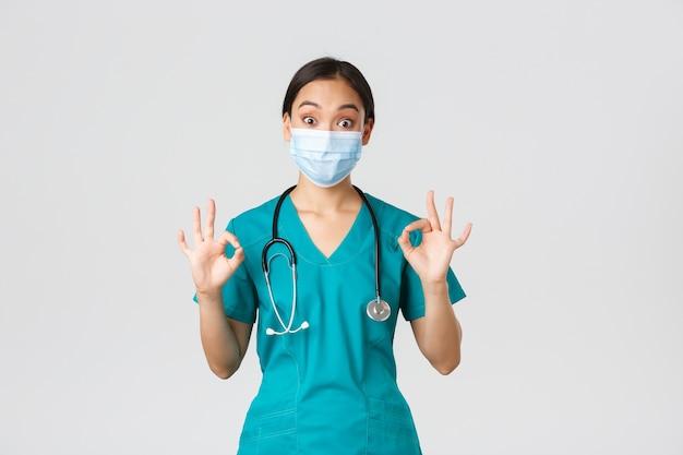 Covid-19、コロナウイルス病、医療従事者の概念。興奮して感動したアジアの女性医師、医療マスクのインターン、承認で大丈夫なジェスチャーを示すスクラブ、白い背景。 Premium写真