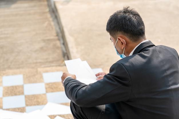 Безработный мужчина, бизнесмен, уволенный с работы, сидевший грустно за пределами офиса, до безработицы из-за ситуации с болезнью covid 19, coronavirus превратился в глобальную чрезвычайную ситуацию. Premium Фотографии