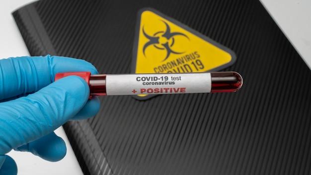 Врач держит в руке коровавирусную вакцину covid 19, зараженный образец крови в пробирке, инъекцию вакцины и шприца. используется для профилактики, иммунизации и лечения от covid-19. Premium Фотографии