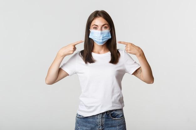 Covid-19、健康と社会的距離の概念。顔に指を指している医療マスクの魅力的なブルネットの少女、白。 無料写真