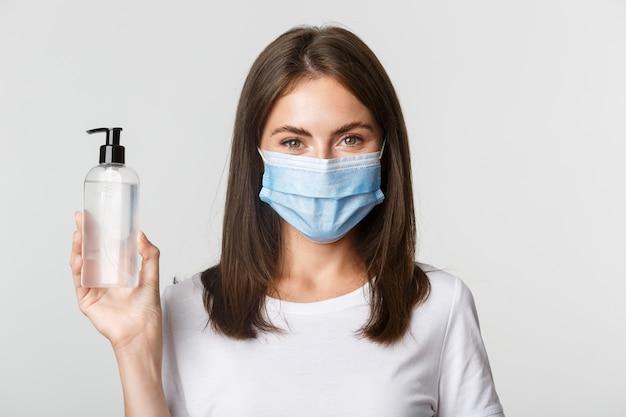 Covid-19, 건강 및 사회적 거리두기 개념. 의료 마스크에 매력적인 웃는 소녀의 근접 손 소독제를 보여주는 방부제를 권장합니다. 무료 사진