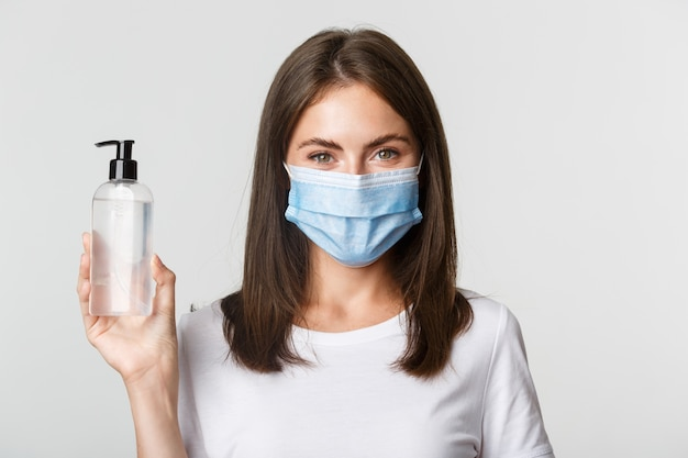 Covid-19, health and social distancing concept. close-up of attractive smiling girl in medical mask, showing hand sanitizer, recommend antiseptic. Free Photo