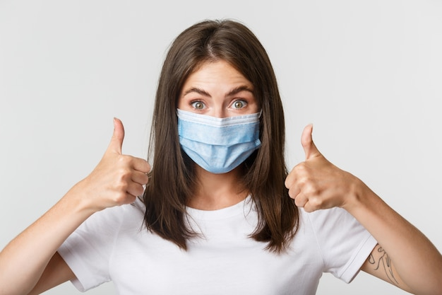 Covid-19, health and social distancing concept. close-up of pleased attractive girl in medical mask showing thumbs-up in approval. Free Photo