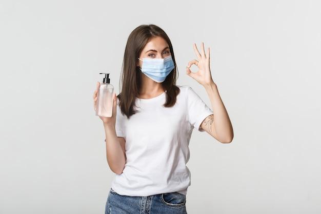 Covid-19, concetto di allontanamento sociale e sanitario. ritratto di ragazza bruna sorridente in mascherina medica, mostrando disinfettante per le mani e gesto giusto. Foto Gratuite